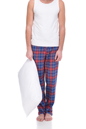 striped pajamas: Young man in sleepwear with pillow in hand isolated on white background.