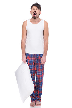 Young, yawning man in sleepwear with pillow in hand isolated on white background. Stock Photo