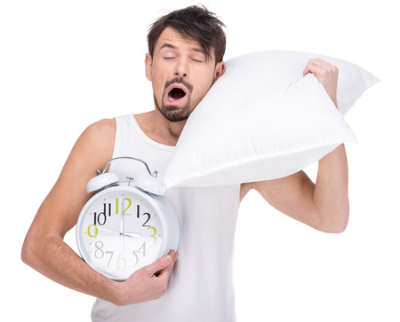 sleepwalking: Young man is sleeping with head resting on pillow with clock on the white background.