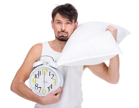 striped pajamas: Young man with head resting on pillow with clock on the white background. Stock Photo