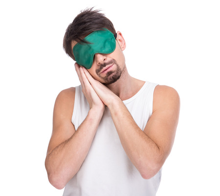 sleep mask: Young man with a sleep mask on the white background.