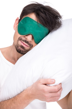 sleep mask: Young man with a sleep mask and pillow on the white background.
