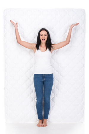 sleep well: Smiling young woman with orthopedic mattress. Quality mattress. Stock Photo