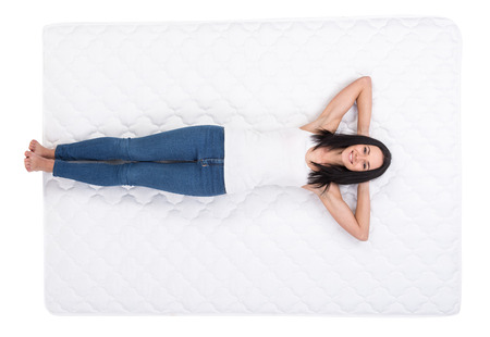 sleep well: Young woman is lying on the bed. Quality mattress.