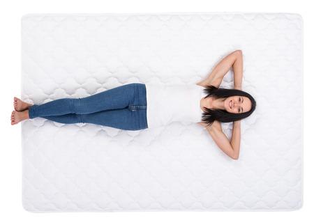 若い女性は、ベッドの上に横たわっています。品質のマットレス。