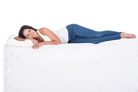 sleep well: Young woman is lying on the mattress. Isolated on white background. Side view.