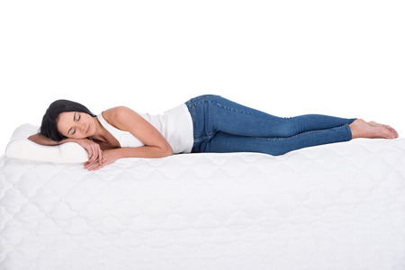 girl lying bed: Young woman is lying on the mattress. Isolated on white background. Side view.