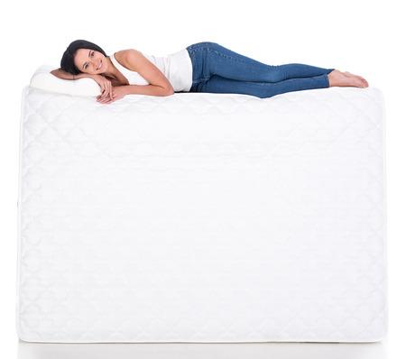 젊은 여자는 매트리스에 누워있다. 흰색 배경에 고립. 측면보기.