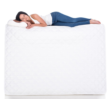 Young woman is lying on the mattress. Isolated on white background. Side view.