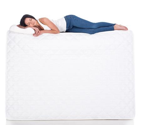 gente durmiendo: Mujer joven est� tumbado en el colch�n. Aislado en el fondo blanco. Vista lateral.