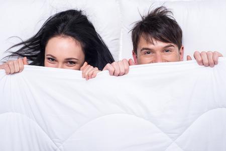 femme sexe: Jeune couple heureux dans un lit. Vue d'en haut. Ils sont � la recherche � la cam�ra.