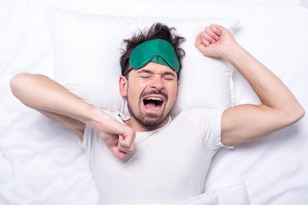 sleep mask: Top view of young sleepy man with sleep mask in the bed.
