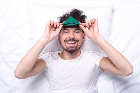 Top view of young smiling man with sleep mask in the bed. photo