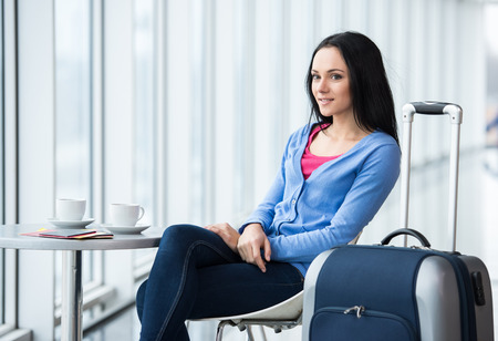 airplane window: Young woman is sitting in the airport with coffee while waiting for flight.