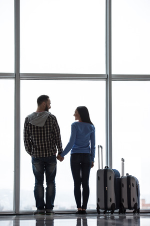 airport window: Young couple with suitcases are looking through airport window while waiting for flight. Back view.