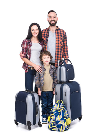 Happy family with luggage are ready to travel. Isolated on white background. Stock Photo