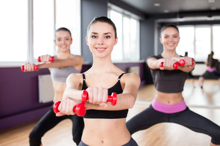 Fitness, sport, training and lifestyle concept. Group of smiling women are stretching in gym with du photo