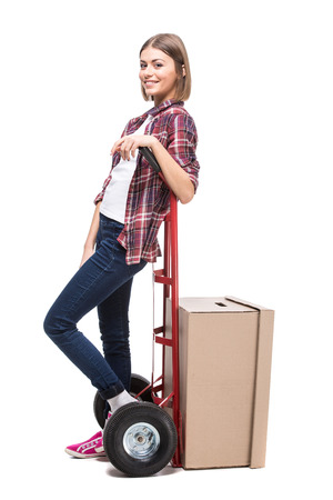 Young woman with paper box and a hand truck, isolated on white background. photo