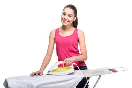 the iron lady: Young smiling woman is ironing a shirt with a steam iron on white background.