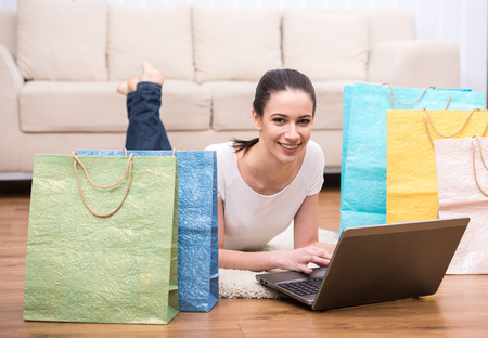 Happy, smiling woman with shopping bags is using laptop, looking at the camera and smiling.