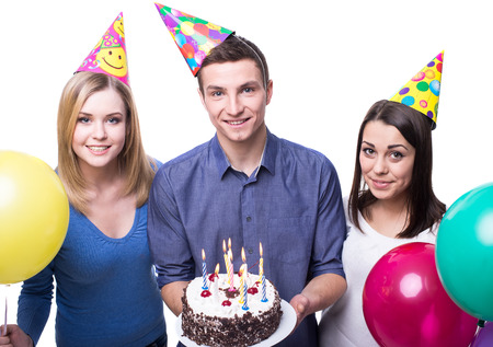 Three young friends having fun on birthday party. White background. photo