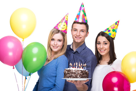 people portraits: Three young friends having fun on birthday party. White background.