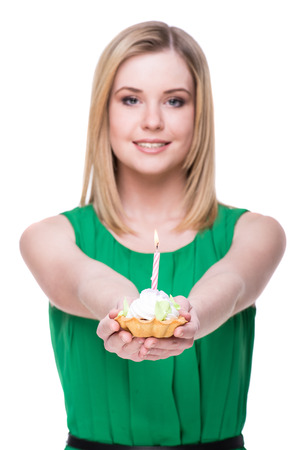 cream cake: Young woman is holding cake with candle. White background.