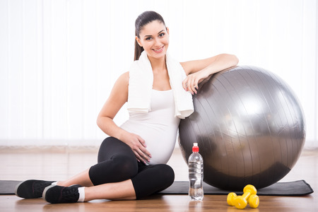pregnancy exercise: Pregnant woman is doing exercises with gymnastic ball.