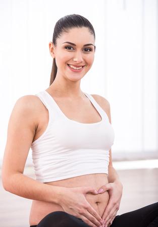 ombligo: Mujer embarazada, concepto coraz�n en el est�mago. Manos que forman el coraz�n en el ombligo femenino.