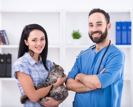 Young woman with her cat on a visit to the vet. photo