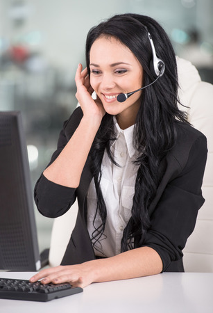 Attractive young woman is working in a call center. Foto de archivo