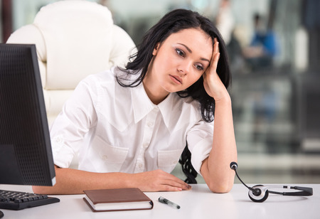 tired: Tired young woman is sitting at the table at work in a call center.