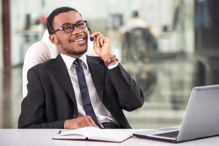 잘 생긴 젊은 사업가 그는 고객 지원 콜 센터에서 쿼리와 거래 헤드셋에 전화를 복용합니다. 스톡 콘텐츠
