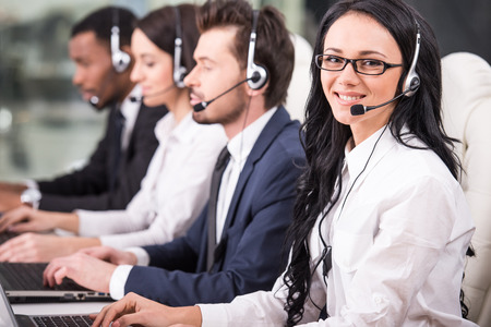 측면 뷰 콜 센터 직원의 라인 미소 하 고 컴퓨터에서 작동합니다.