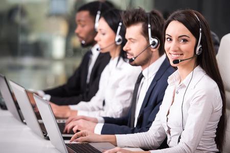 Çağrı merkezi çalışanlarının hattının Yandan görünüm gülümseyen ve bilgisayarlarda çalışıyor.