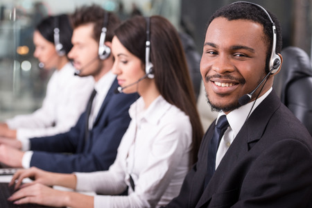 측면 뷰 콜 센터 직원의 라인 미소 하 고 컴퓨터에서 작동합니다. 그들 중 하나는 피곤하고 자고 있습니다.