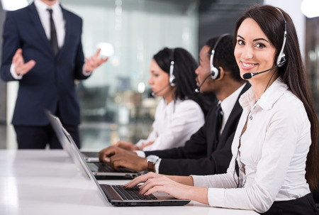 Manager is explaining something to employees in a call centre photo