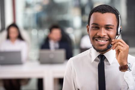 笑顔の幸せな顧客の肖像画は、職場の電話演算子をサポートします。
