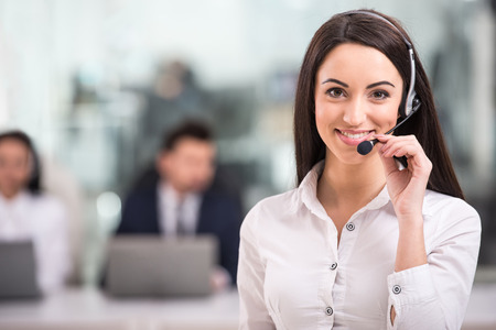 to phone calls: Portrait of happy smiling female customer support phone operator at workplace.