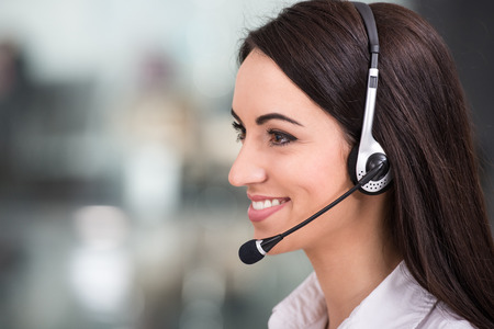 Close-up, side view of attractive young woman is working in a call center.