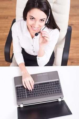 魅力的な若い女性の平面図は、コール センターで働いています。