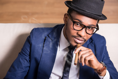 Young black man is wearing suit and hat, smoking a cigar. photo
