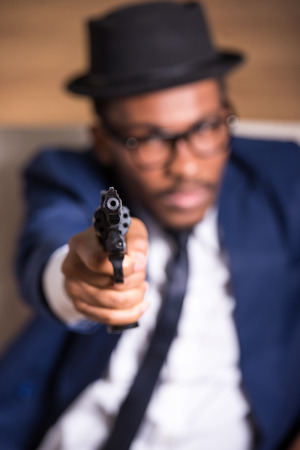 Young black man is wearing suit and hat with gun. Focus on gun. photo