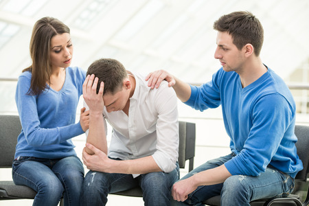 Feeling pain and depression. Depressed young man is sitting at the chair while two other people are comforting his. Фото со стока