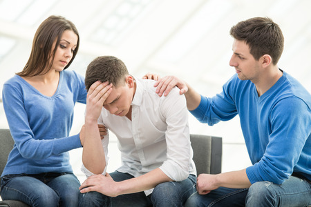 Feeling pain and depression. Depressed young man is sitting at the chair while two other people are comforting his. Фото со стока - 35457546