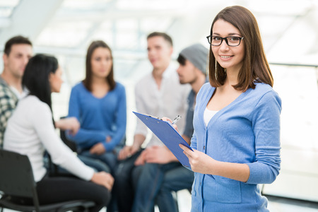 support group: Young woman with a tablet and a group of people in the background.