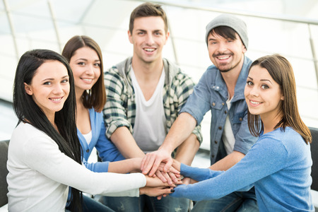 joining hands: Group of young and diverse people are joining hands. Smiling and looking at the camera. Stock Photo