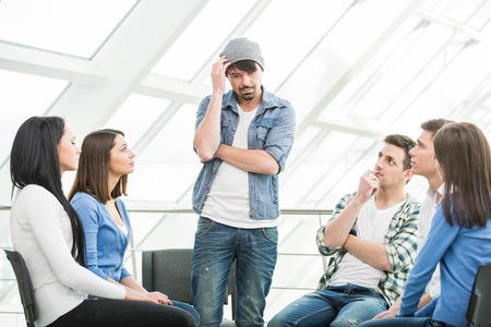 terapia grupal: Hombre joven est� compartiendo sus problemas con la gente. Vista del hombre est� diciendo algo y gesticulando mientras que el grupo de personas que est�n sentados frente a �l y escuchar.