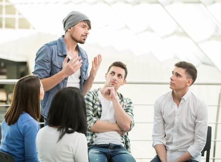 Il giovane è condividere i suoi problemi con la gente. Vista l'uomo sta dicendo qualcosa e gesticolare mentre il gruppo di persone sono seduti di fronte a lui e di ascolto. Archivio Fotografico - 35457728