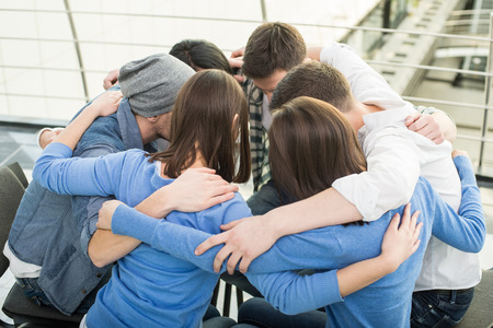 Circle of trust. Group of people are sitting embracing in circle  and supporting each other. photo